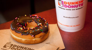 A chocolate glazed donut and a cup of coffee are arranged for a photograph at a Dunkin' Donuts Inc. store in West Orange, New Jersey, U.S., on Thursday, July 7, 2011. Sales at U.S. retailers surpassed analysts' estimates last month as discounts and lower gas prices in the U.S. enticed consumers to spend. Photographer: Emile Wamsteker/Bloomberg
